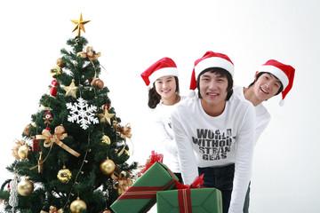 산타 모자를 쓴 젊은 사람들과 크리스마스트리