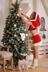 Sexy Santa Claus girl putting Christmas ornaments on the tree