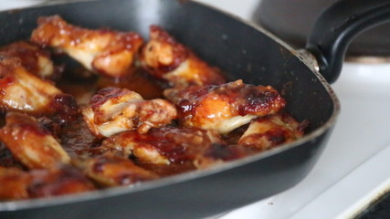 Video with delicious chicken wings and sauce in grill pan.