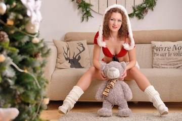 Santa girl in Christmas costume with teddy bear sits on sofa