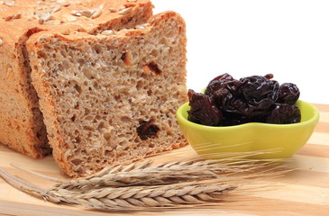 Baked wholemeal bread, dried plums and ears of wheat