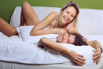 Smiling and joyful couple  joking in bed