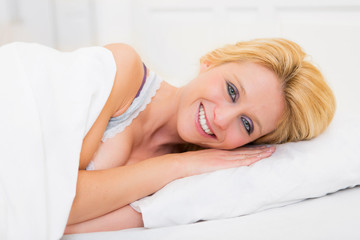 Young attractive blonde woman sleeping in a bed