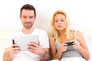 Young attractive couple using mobile and tablet in bed