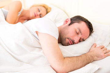 Young attractive couple sleeping in a bed