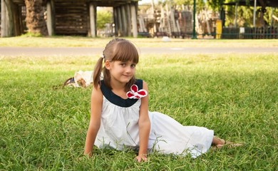 Cute little girl in white dress sitting on  lawn in  park