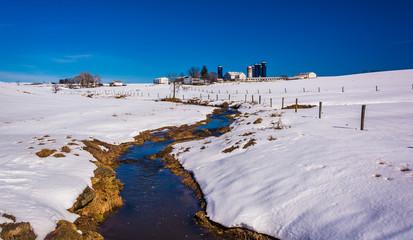 Stream through a snow covered farm field in rural Lancaster Coun