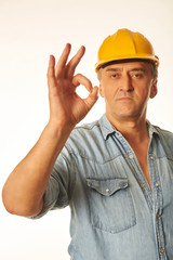 Worker in a yellow hardhat showing OK gesture