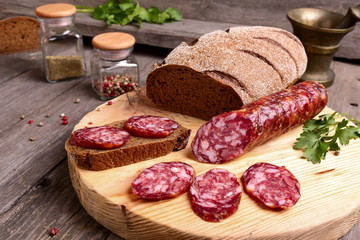 Sliced salami and bread on a cutting board