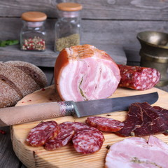 Sliced cold meats on a cutting board, square photo
