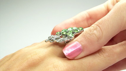jewelery ring with green emerald crystals putting on the finger