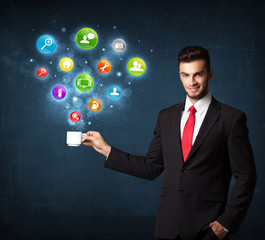 Businessman holding a white cup with setting icons