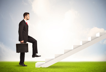 Business person climbing up on white staircase in nature
