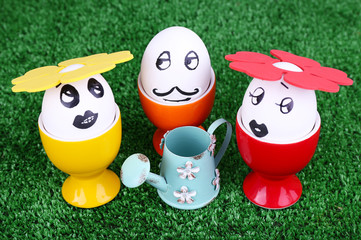 Eggs in egg cups with watering can on green background
