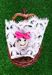 Single egg on lace napkin in wicker basket on green background