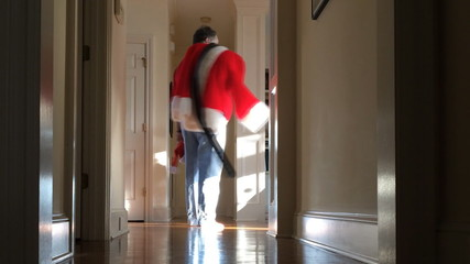 Tired Santa walks down hall, turns and nods