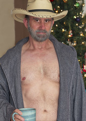 A Cowboy in an Open Robe by a Christmas Tree