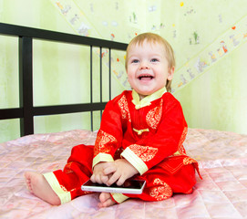 Довольный малыш сидит на кровати с сотовым телефоном в руках