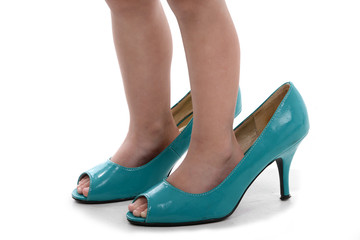 Child`s feet in shoes with heels