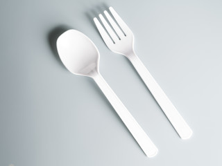 white plastic spoon and fork on gray