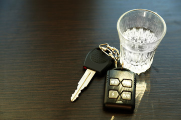 Glass of alcoholic drink and car key, on wooden table