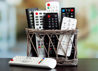Many remote control devices in basket on bright background