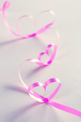 Ribbon shaped as hearts on gray background