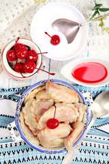 Vareniki with cherry in pan on tablecloth close-up