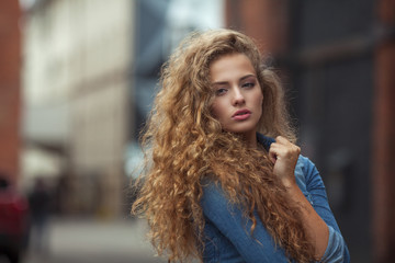 Beautiful young girl with thick long curly hair outdoors