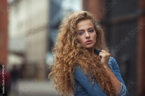 Leinwanddruck Bild Beautiful young girl with thick long curly hair outdoors