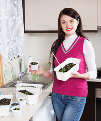 woman with  seedlings at home kitchen