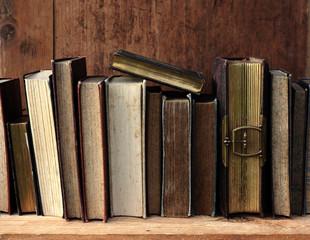 alte Bücher in braunem Holzregal.