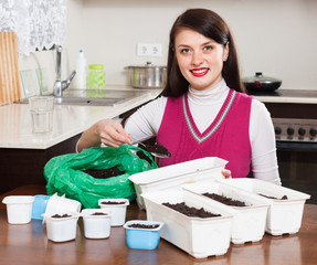 Brunette woman making ground in pots for seedlings