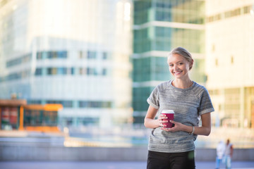 Girl drinking coffee in business district of Paris