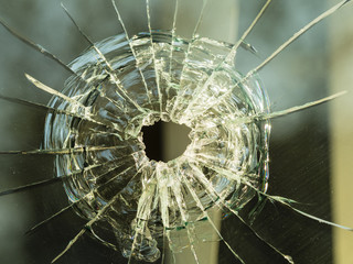 bullet hole on glass making cracks