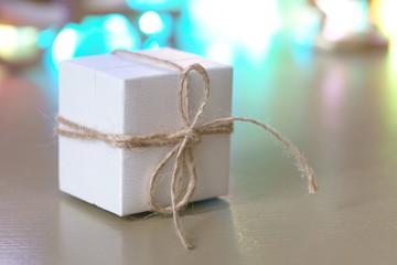 Маленькая белая коробка на комоде на фоне гирлянд