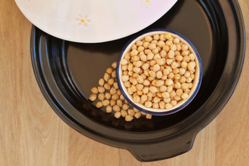 Overhead view of bowl filled with chick peas inside a tagine
