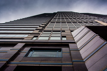 Looking up at a modern building under a cloudy sky in Philadelph