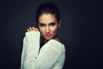 Beautiful woman in white sweater posing in studio on dark backgr