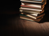Pile of hardcover books in a shadowy room poster