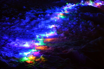 burning сhristmas lights garland on the snow at night
