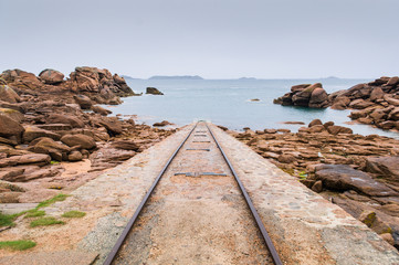 Old pier in a beach full of rocks, Brittany, France