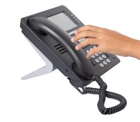 Female hand picking up desktop telephone handset