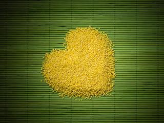 Millet groats heart shaped on green mat surface.