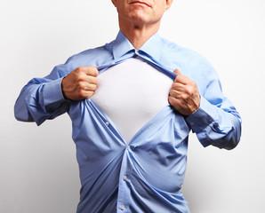 Superhero. Mature businessman tearing his shirt off over white b