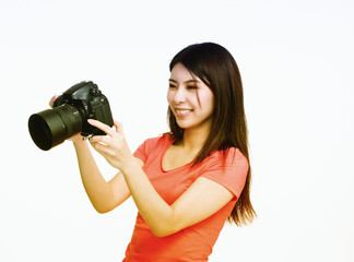 Young asian female photographer happy looking at camera pictures