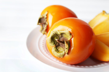 Ripe persimmons on plate, on wooden background
