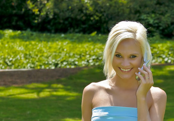 Beautiful blond woman using cell phone  outdoors