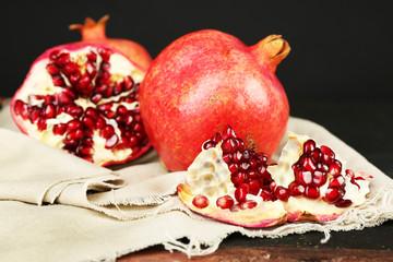 Juicy ripe pomegranates on dark background