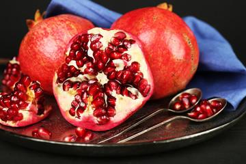 Juicy ripe pomegranates on metal plate, on dark background